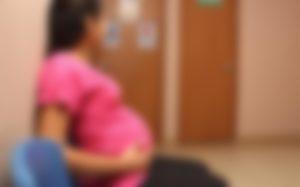 Mujer jóven embarazada en una sala de espera de un centro de salud